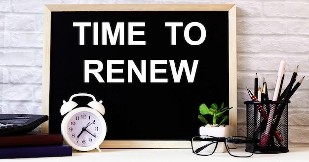 As palavras hora de renovar estão escritas no quadro-negro ao lado do despertador branco, óculos, vasos de plantas e lápis em um suporte.