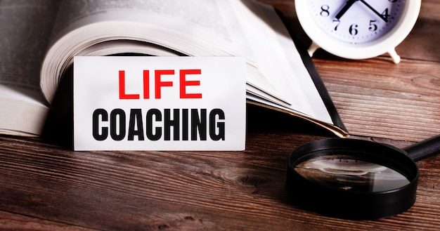 As palavras life coaching escritas em um cartão branco perto de um livro aberto, despertador e lupa