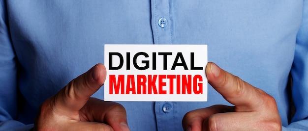 As palavras marketing digital estão escritas em um cartão de visita branco nas mãos de um homem