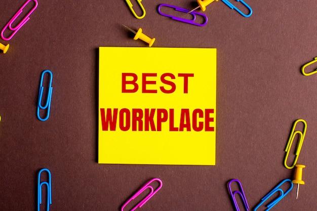 As palavras melhor local de trabalho estão escritas em vermelho em um adesivo amarelo em uma superfície marrom ao lado de clipes de papel multicoloridos