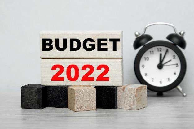 As palavras orçamento 2022 escritas em cubos de madeira com um despertador.