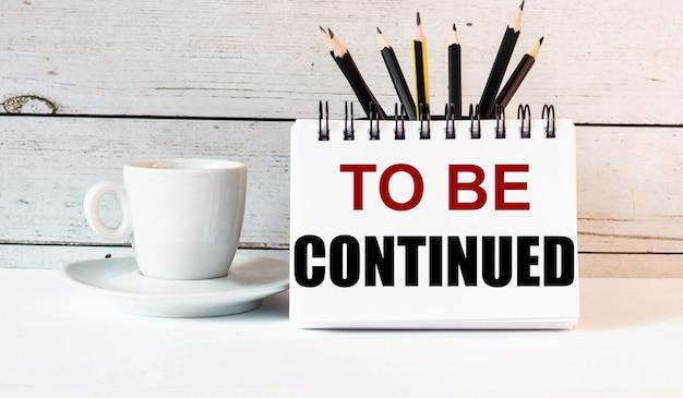 As palavras para continuar estão escritas em um bloco de notas branco perto de uma xícara de café branco sobre um fundo claro