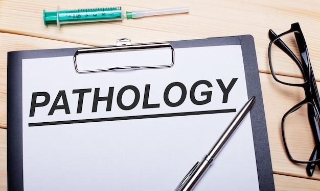 As palavras patologia estão escritas em um pedaço de papel branco ao lado de óculos de aro preto, uma caneta e uma seringa.