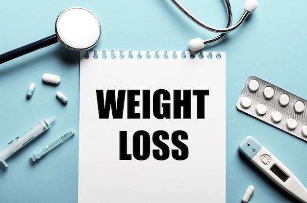 As palavras perda de peso escritas em um bloco de notas branco sobre uma superfície azul perto de um estetoscópio, seringa, termômetro eletrônico e comprimidos. conceito médico