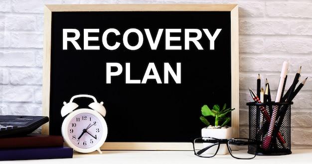 As palavras plano de recuperação estão escritas no quadro-negro ao lado do despertador branco, copos, vasos de plantas e lápis em um suporte.