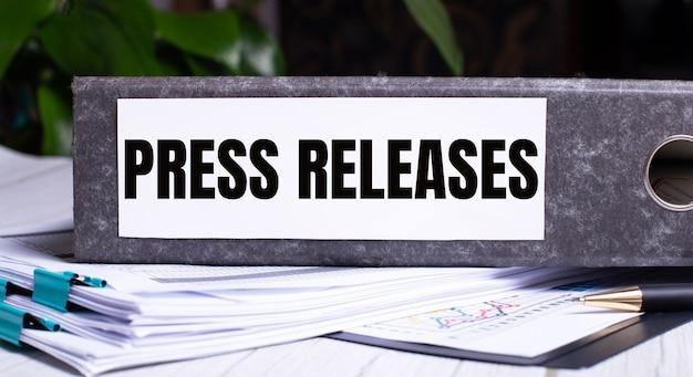 As palavras press releases escritas em uma pasta cinza ao lado dos documentos. conceito de negócios