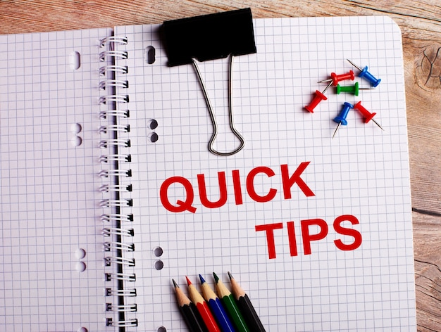 As palavras quick tips estão escritas em um caderno perto de lápis e botões multicoloridos em uma superfície de madeira
