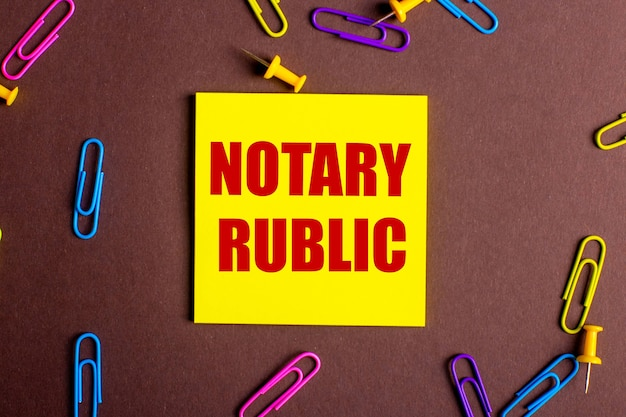 As palavras tabelião público estão escritas em vermelho em um adesivo amarelo sobre fundo marrom ao lado de clipes de papel multicoloridos.