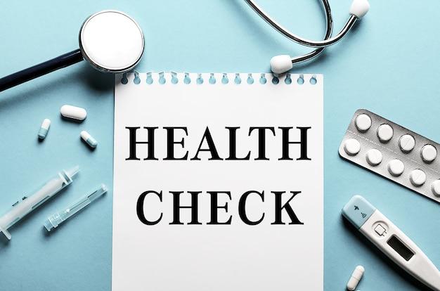 As palavras verificação de saúde escritas em um bloco de notas branco em uma superfície azul perto de um estetoscópio, seringa, termômetro eletrônico e comprimidos