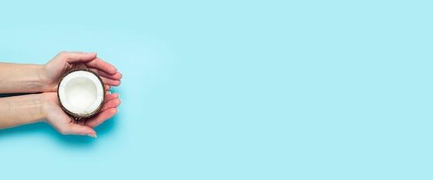 As palmas femininas seguram a metade aberta de um coco sobre um fundo azul. vista superior, configuração plana. bandeira.