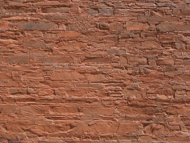 As paredes são de pedra, misturadas com solo laranja.