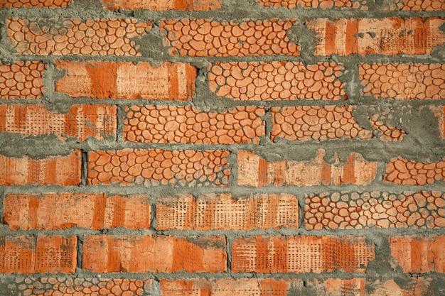 As paredes são tijolos de argila vermelha texturizados com padrão. plano de fundo de uma nova casa de tijolos com cimento.