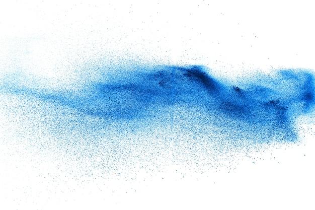 As partículas de poeira azuis da cor espirram no fundo branco.