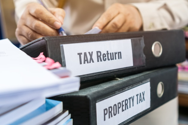 As pastas da declaração de impostos e do imposto sobre a propriedade empilham-se com etiqueta preta no relatório de resumo de documentos de papelada