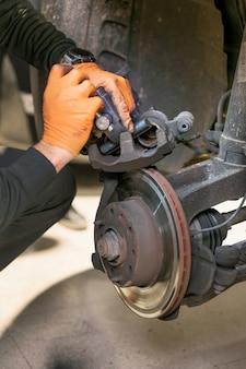As pastilhas de freio de reparo de mecânico de automóveis fecham.