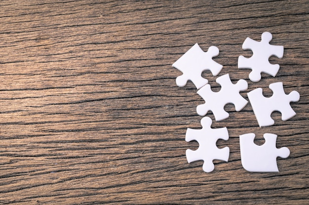As peças brancas do quebra-cabeça encontram-se em um de madeira