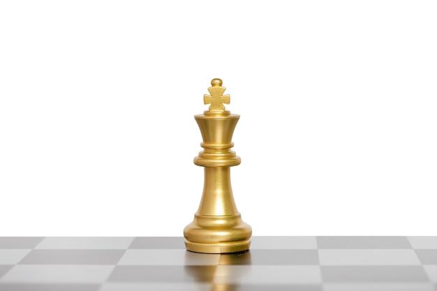 As peças de xadrez do rei, xadrez do rei dourado em um tabuleiro de xadrez. isolado no fundo branco. conceito de líder de negócios. trajeto de grampeamento.