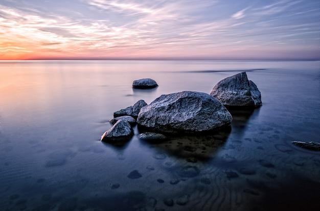 As pedras no mar ao pôr do sol.