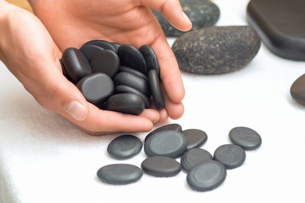 As pedras pretas da massagem nas mãos do homem fecham-se acima.