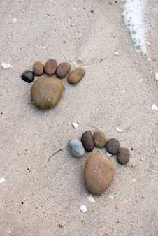 As pedras são dispostas em forma de pés na areia da praia.