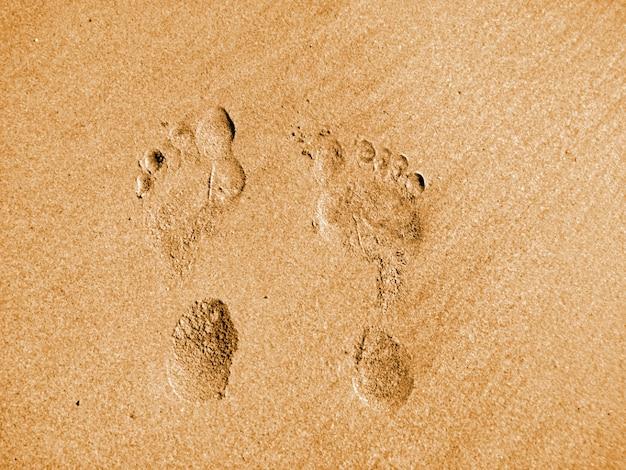 As pegadas do homem na praia de areia em férias de férias relaxante tempo