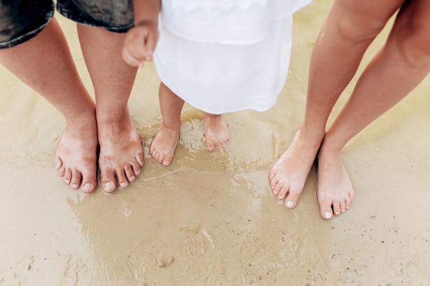 As pernas da família com a filha pequena na praia. pernas pai, mãe, filhas