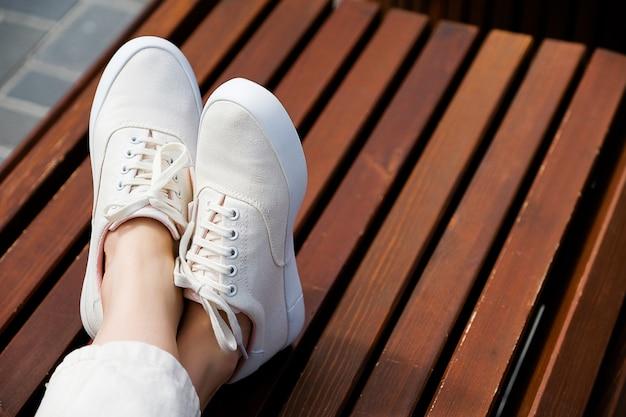 As pernas da garota em novas sapatilhas brancas e jeans