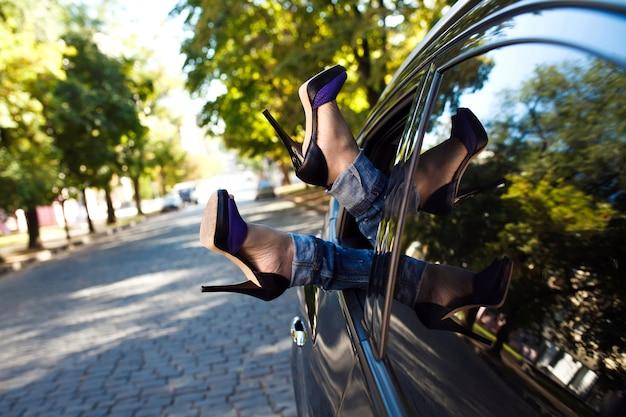 As pernas da mulher para fora da janela do carro.
