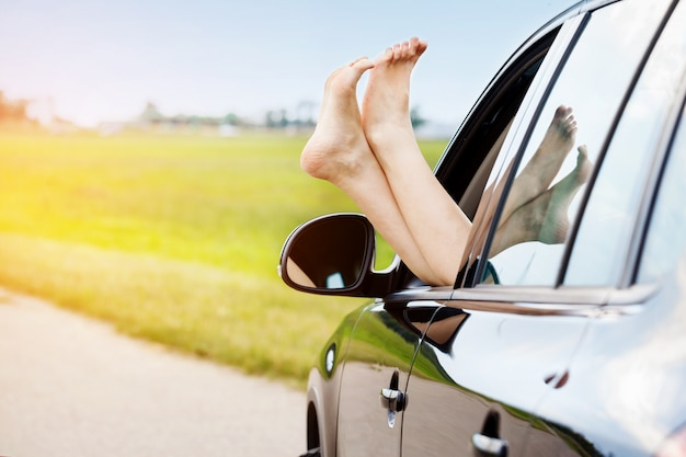 As pernas da mulher para fora da janela do carro