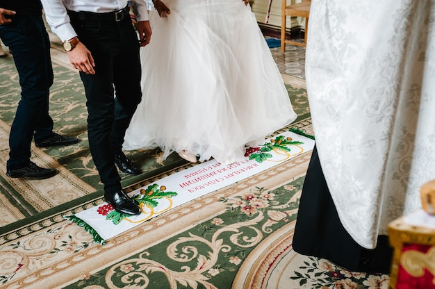 As pernas da noiva e do noivo ficam sobre toalha bordada, tradicionalmente em uma cerimônia de casamento na igreja. aparecem da parte inferior às pernas.