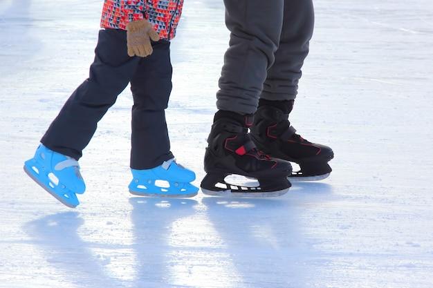 As pernas da pista de patinação no gelo infantil e adulto