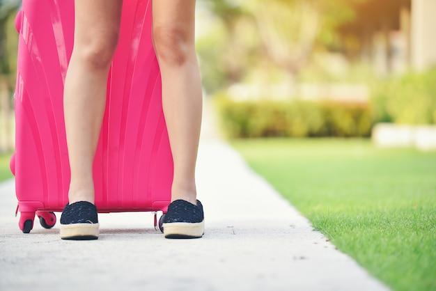 As pernas das mulheres usavam sapatos pretos com malas rosa e estavam preparadas para sair.