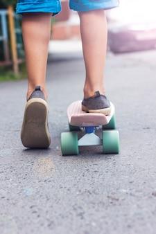 As pernas de criança menino no skate descendo a calçada, vertical, tonificada foto