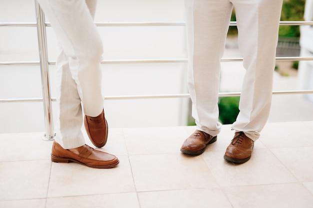 As pernas de dois homens em pé na varanda, close-up