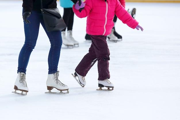 As pernas de um adulto e uma criança patinando na pista de gelo
