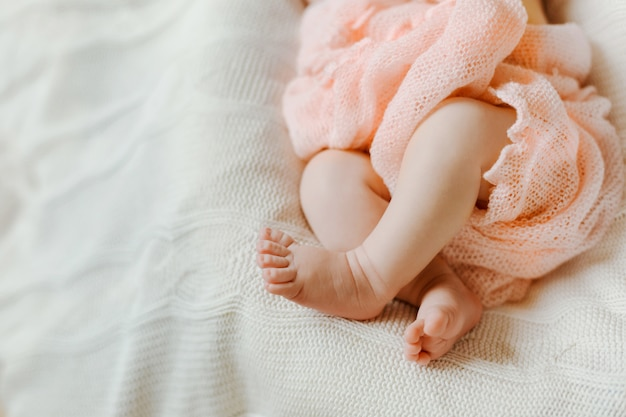 As pernas de um bebê recém-nascido envolto em um cobertor rosa deitado no cobertor de malha