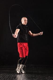 As pernas de um homem musculoso com treinamento de kickboxing corda para pular no preto