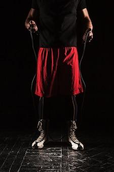 As pernas de um homem musculoso com treinamento de kickboxing corda pular no preto
