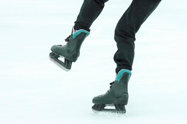 As pernas de um homem patinando em uma pista de gelo. esportes, hobbies e recreação de pessoas ativas