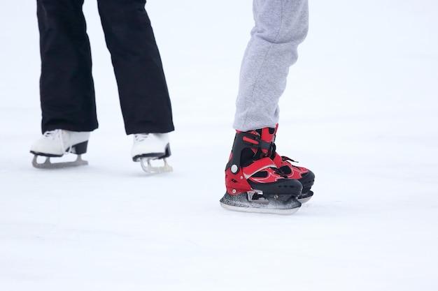 As pernas de um homem patinando em uma pista de gelo