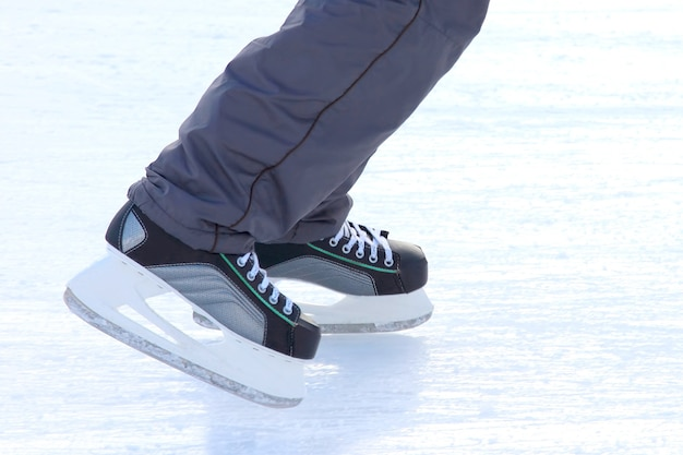 As pernas de um homem patinando na pista de gelo. esportes, hobbies e recreação de pessoas ativas