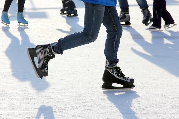 As pernas de um homem patinando na pista de gelo