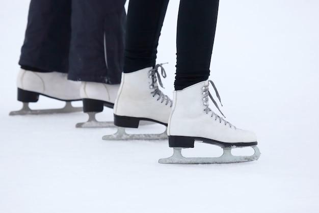 As pernas de um homem rolando de patins na pista de gelo