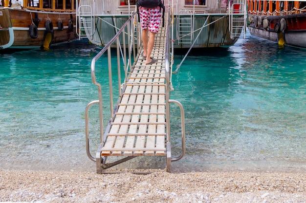 As pernas de um homem sobem no navio ao longo da escada