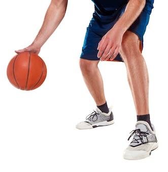 As pernas de um jogador de basquete com bola