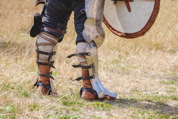 As pernas do cavaleiro em armadura de combate. o cavaleiro aguarda o início da batalha