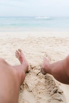As pernas do homem de close-up na praia