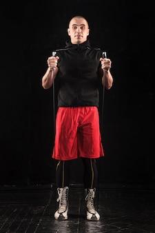 As pernas do homem musculoso com pular corda