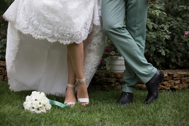As pernas dos noivos estão na grama verde e no buquê de casamento