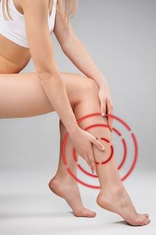 As pernas femininas e as mãos no fundo branco